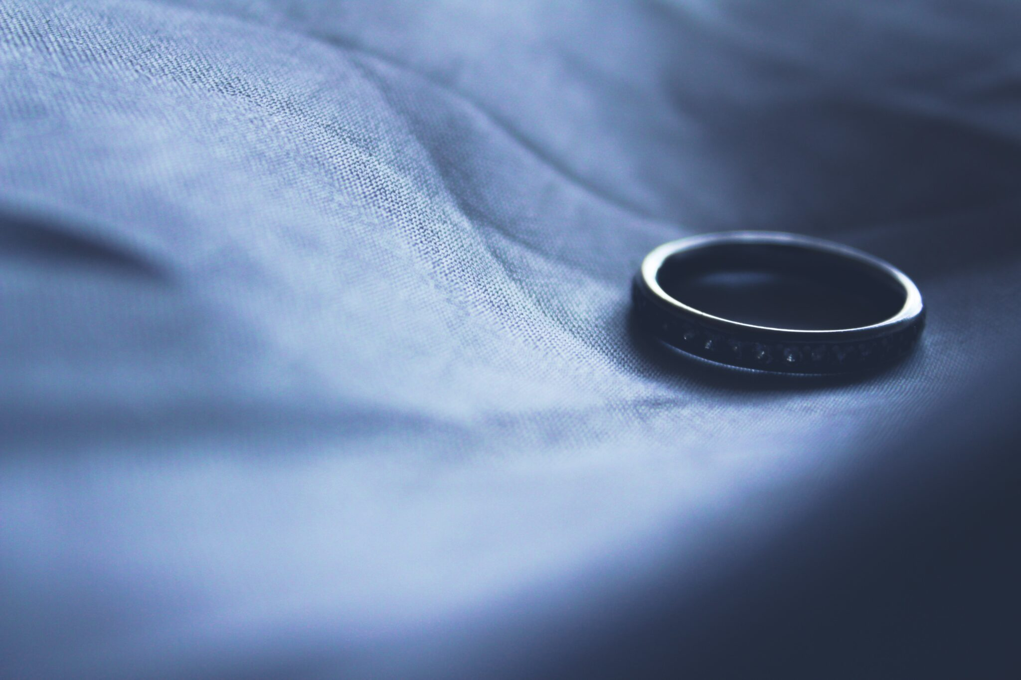 Single wedding ring laying on fabric, for BGS Law blog on Difference Between Absolute and Limited Divorces